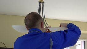 Electrician guy changing light bulbs in chandelier. Back view. stock video footage