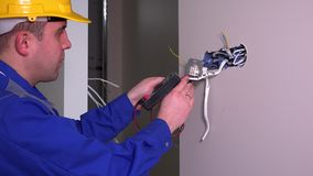 Electrician guy checking socket voltage using multimeter in wall fixture socket. Static shot. 4K UHD stock video
