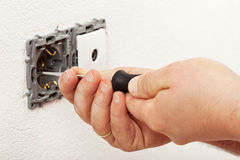Electrician hand mounting a wall fixture. Fastening the screws Stock Image