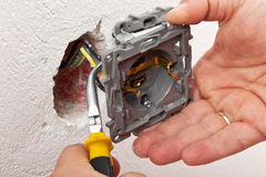 Electrician hand mounting a wall fixture. Fitting the wires with pliers Stock Photos