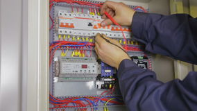 Electrician hands checking circuit breakers in electrical fuse box. HD stock video footage