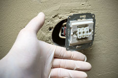 Electrician hands in gloves installing light switch in wall Stock Photography