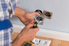 Electrician hands installing wall socket royalty free stock photo