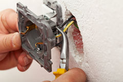 Electrician hands installing wires into electrical outlet stock photo