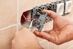 Electrician hands installing wires into a wall fixture. Using pliers - closeup Stock Photos