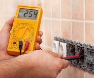 Electrician hands measuring voltage in electrical wall socket wi. Th multimeter - closeup royalty free stock images