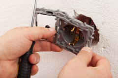 Electrician hands mounting electric wall fixture Stock Images