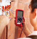 Electrician hands with multimeter - closeup. Electrician hands with multimeter - measuring and installing electrical wires, closeup royalty free stock image