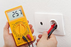 Electrician hands with multimeter. Measuring voltage in electrical wall fixture royalty free stock photography