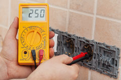 Electrician hands with multimeter measuring the voltage in a wall fixture. Electrician hands with multimeter measuring the voltage in a partially installed wall royalty free stock photography