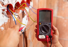 Electrician hands with multimeter and wires. Electrician hands with multimeter measuring the wires in a new building - closeup royalty free stock photos