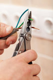 Electrician hands with pliers and wires Stock Image