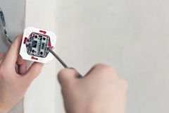 Electrician Hands With Screwdriver. Installing Wall Socket stock photo