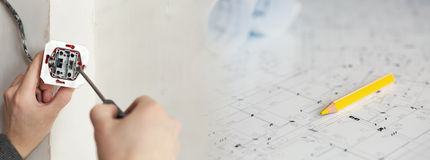 Electrician Hands With Screwdriver Installing Wall Socket with a blueprints on a background Stock Photo