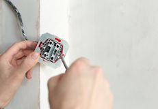 Electrician Hands With Screwdriver Installing Wall Socket. Close-up Of Electrician Hands With Screwdriver Installing Wall Socket royalty free stock image