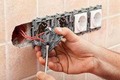 Electrician hands tighten electrical wires in wall fixture or so Royalty Free Stock Photo