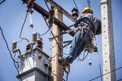 Electrician hanging on the electricity pole stock images