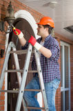 Electrician in hardhat standing stepladder and repairing lamp on Stock Photography
