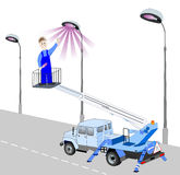Electrician has replaced the bulb on a lamppost. Smiling electrician standing in the cradle of autohydraulic, points to a glowing lamp lamppost Royalty Free Stock Image
