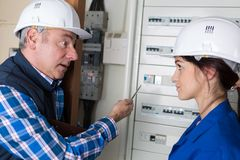 Electrician and female apprentice checking electrical outlet. Electrician and his female apprentice checking an electrical outlet royalty free stock photography