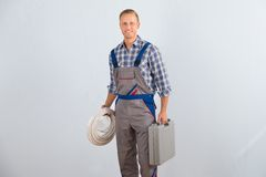 Electrician holding cables and toolbox. Young Happy Electrician Holding Cables And Toolbox Royalty Free Stock Photography