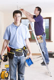Electrician holding drill and cable spool with co-worker wiring ceiling in background Stock Photos