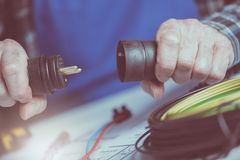 Electrician holding electrical plugs. Electrician hands holding electrical plugs Royalty Free Stock Photo