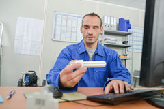 Electrician holding light bulb Royalty Free Stock Image