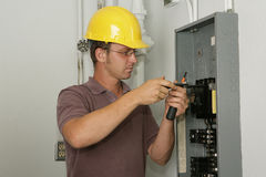 Electrician Industrial Panel. An electrician working on an industrial breaker panel.  Model is an actual electrician performing all work to industry codes and Stock Images