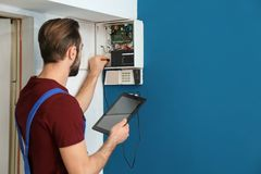 Electrician inspecting alarm system stock photo