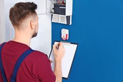 Electrician inspecting alarm system royalty free stock photos