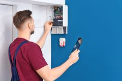 Electrician inspecting alarm system stock photography