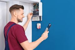 Electrician inspecting alarm system stock image