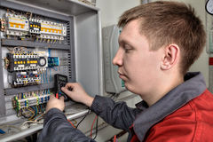Electrician inspecting fuse box in industrial switchboard. royalty free stock photography