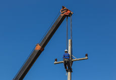 Electrician install wire on electric power pole with crane Stock Photo