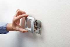 Electrician installing AC power socket Stock Image