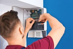 Electrician installing alarm system stock image
