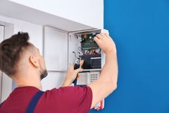 Electrician installing alarm system stock photography