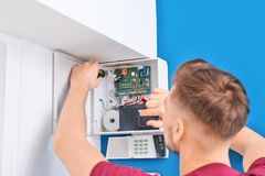Electrician installing alarm system stock images