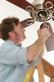 Electrician Installing Ceiling Fan. An electrician installing a new ceiling fan. All work is being performed to code by a licensed master electrician stock image