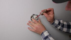 An electrician is installing contact. Home improvement. In natural light stock video