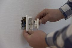 An electrician is installing contact. Home improvement. In natural light Royalty Free Stock Image