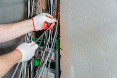An electrician is installing electric wires. stock photos