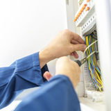 Electrician installing an electrical fuse box. In a house working with pliers on the wiring circuits royalty free stock photography
