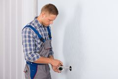 Electrician installing electrical socket Stock Images