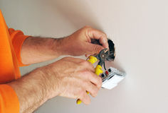 Electrician installing electrical switches in the new house stock photo