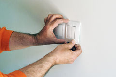 Electrician installing electrical switches in the new house. A qualified electrician placing white electrical switches during the renovation of the house stock photos
