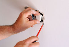 Electrician installing electrical switches. A qualified electrician placing white electrical switches during the renovation of the house royalty free stock photography