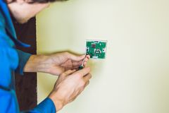 Electrician installing an electrical thermostat in a new house stock photo
