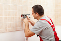 Electrician installing electrical wall fixture. Fastening the wires in the receptacle Royalty Free Stock Image
